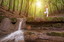 Relaxation, Woman practices yoga at the waterfall Stock Image
