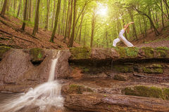 Relaxation, Woman practices yoga at the waterfall Stock Photo