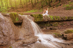 Relaxation, Woman practices yoga at the waterfall Royalty Free Stock Photo