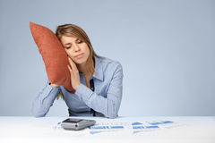 Relaxation in work (burnout). Woman having a rest (sleep, relax, snooze, nap, doze) in work. Burnout tired worker. Weary woman with pillow, graphs, sheets and Stock Photos