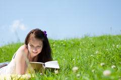 Relaxation. Young beautiful girl relaxing on a meadow with a book Stock Images
