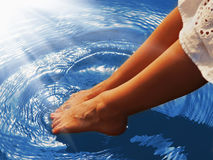 Relaxation. Young woman wets feet in water. Sea, ocean, travel