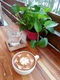 Relaxe com um copo do latte do caffe com arte do latte da flor Imagens de Stock Royalty Free