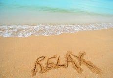 Relaxe escrito na areia Imagens de Stock Royalty Free