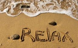 Relaxe - a inscrição na areia perto do oceano Imagem de Stock Royalty Free