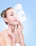 Relaxe a jovem mulher com máscara do facial de pano fotos de stock royalty free