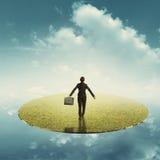 Relaxe a mulher de negócio que guarda o saco na terra de flutuação da grama sobre o céu imagens de stock