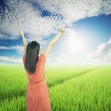 Relaxe a mulher em campos do arroz e no céu verdes de Sun Fotografia de Stock