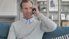 Relaxe o homem envelhecido médio que usa Smartphone ao sentar-se no sofá video estoque