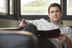 Relaxed бизнесмен сидя на софе с папкой Стоковые Изображения RF