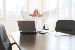 Relaxed бизнесмен сидя на столе в офисе стоковое изображение