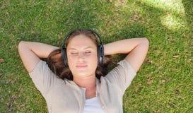 Relaxed женщина слушая к музыке пока лежащ на лужайке Стоковые Изображения