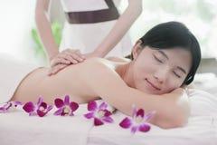 Relaxed женщины получая массаж, цветки Стоковые Изображения RF