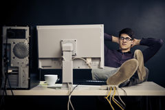 Relaxed Admin At His Desk. Young man with glasses sitting in front of his computer royalty free stock images