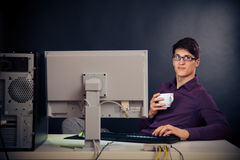 Relaxed Admin At His Desk. Young man with glasses sitting in front of his computer stock images