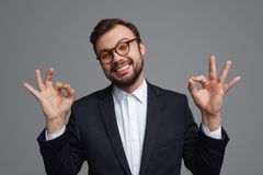 Relaxed adult businessman showing OK gestures stock images