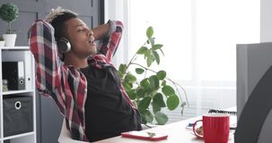 Relaxed businessman singing and listening music using headphones at office stock footage