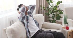Man enjoying music through headphones at home. Relaxed african american man having fun listening to music through headphones at home stock video