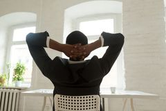 Relaxed African American resting leaning back in chair royalty free stock photo