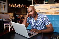 Relaxed african man at a cafe table using laptop Stock Images