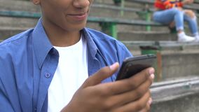 Relaxed afro-american male teen watching prank video on cellphone and smiling