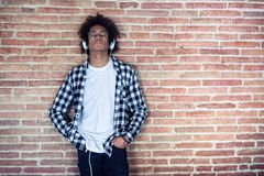 Relaxed afro-american young man listening to music with headphones leaning on stone wall at home royalty free stock image