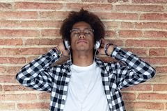 Relaxed afro-american young man listening to music with headphones leaning on stone wall at home stock photo