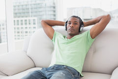 Relaxed Afro man with headphones sitting on sofa in house Stock Photo