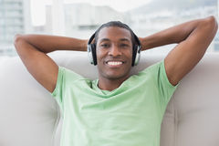 Relaxed Afro man with headphones sitting on sofa Royalty Free Stock Image