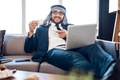 Relaxed arab businessman on lapton with coffee on couch at hotel room. stock image