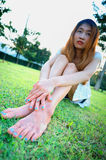 Relaxed asia young woman with bare feet sitting on grass Stock Image