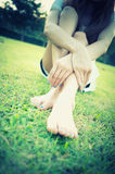 Relaxed asia young woman with bare feet sitting on grass Royalty Free Stock Images