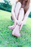 Relaxed asia young woman with bare feet sitting on grass Stock Images