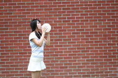 Relaxed Asian Chinese girl blow up a ballon and enjoy free time on the lawn. Asian Chinese woman enjoy free time at school, hold a bottle of water, and carry a Royalty Free Stock Images