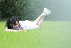 Relaxed Asian Chinese girl enjoy free time on the lawn. Asian Chinese woman enjoy free time at school, hold a bottle of water, and carry a piece of biscuit in Royalty Free Stock Photos