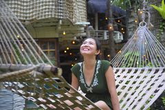 Relaxed Asian Chinese woman on her 20s wearing green Summer dress sitting happy joyful and comfortable on beautiful hammock bed Stock Images