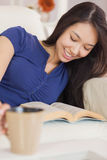 Relaxed asian girl lying on the sofa reading a novel and drinkin Stock Photography