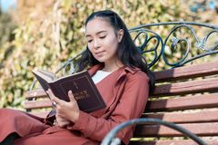 Relaxed Asian girl reading Holy Bible on air. Concentrate on thoughts. Charming international girl sitting in park while enjoying her favorite book royalty free stock photography