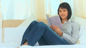Relaxed asian woman reading a book stock video footage