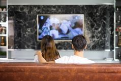 Relaxed asian young couple watching tv at home in bright living. Room,Woman using the control remote Royalty Free Stock Images