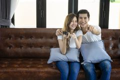 Relaxed asian young couple watching tv at home in bright living. Room,Woman using the control remote Royalty Free Stock Image