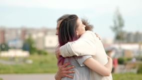 A relaxed attractive middle-aged man with long gray hair and a young woman with dyed hair hugging and greeting. Meeting an adult daughter and father stock footage