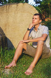 Relaxed attractive smiling man sit in a shirt, shorts and hours near large stone Stock Photography
