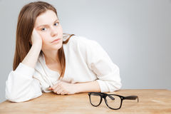 Relaxed attractive teenage girl with glasses sitting at the table Royalty Free Stock Image