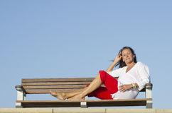 Relaxed attractive woman bench outdoor Stock Photo