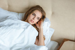Relaxed attractive young woman waking up in bed Stock Photography