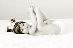 Relaxed baby. Beautiful angel sleeping on bed holding her legs up Royalty Free Stock Photo