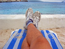 Relaxed at the Beach. A man rests on a lounger at the beach and overlooks the ocean Royalty Free Stock Image
