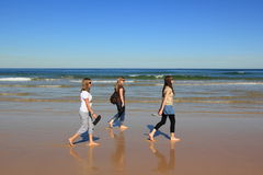 Woman beach walk. Three relaxed women walking barefoot at a beach on a sunny day at the Central Coast, Australia Royalty Free Stock Photos
