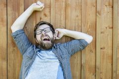 A relaxed bearded, Caucasian man funny yawns and stretches, outdoors on a summer day. , on the background of painted old. Wooden surface. Close-up stock images